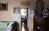 Rosafarbener Schlafraum mit Antiquitäten und Blick durch offene Tür auf Arbeitsecke