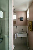 Pink bathroom with a white sink and small windows