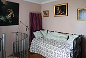 Bett mit Metallgestell im rosafarbenem Zimmer und Treppengeländer in Edelstahl