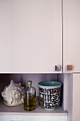 Open storage area in a pink cupboard - cups, bottles and snail shell