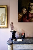 Still life - decorative objects on a stone mantelpiece in front of a pink wall