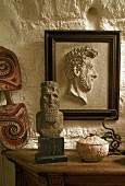 Framed half relief on a rustic stone wall and stone busts on a wooden table top