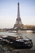 Sunny day in Paris - house boat docked on the bank with a view of the Eiffel tower