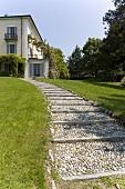 Gravel path through a garden and an elegant villa