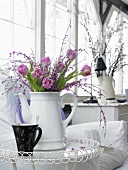 A bunch of pink tulips and flowering twigs in a white porcelain jug on an occasional table