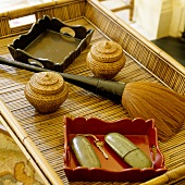 An arrangement on a bamboo tray with a varnished wooden bowl, mini wicker baskets and a bushy brush