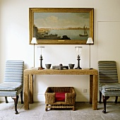 Rustic wooden sideboard, with table lamps and two black and white striped chairs