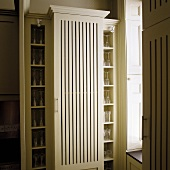 Light colored kitchen cupboard with slits in the front and built in shelves with glass