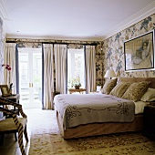An English style bedroom with window doors, a double bed and floral patterned wall paper