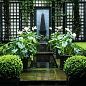 White flowers in pots in stone pools with water in a garden and black trellises on the house