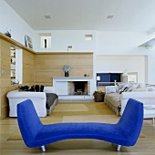 A blue divan and a white sofa set in an open-plan living room with a wood panelled wall and a fireplace