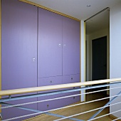 A built in cupboard with purple doors on a gallery and a banister rail with ropes