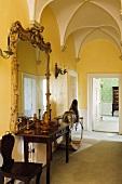Gelber Flur mit Kreuzgratgewölbe und barockem Spiegel über Wandtisch und Blick auf offene Tür