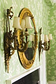 Lamps and a gold-framed mirror on a wall with floral wall paper