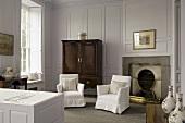 Bad im eleganten Landhausstil mit weissen Hussen Sesseln vor Kamin und fliederfarbenen Wänden