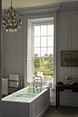 Badezimmer im eleganten Landhausstil mit freistehender Badewanne vor Fenster mit Aussicht