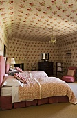 A bedroom with single beds and a floral pattern on the walls and ceiling
