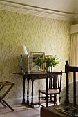Schlafraum mit antikem Wandtisch und Tischlampe vor Tapete mit floralem Muster