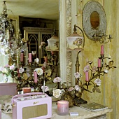 A gilded candle holder, an antique table lamp and a pink portable radio in front of a wall mirror