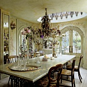 A dining room in a Baroque castle - a crystal chandelier hanging above a marble-topped table with metal legs and arched doors leading onto a terrace