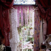 Dresses hanging on the wall in front of a opening with a fringe curtain and gathered red material with a view onto a conservatory