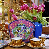 A shiny golden tea service with a tea cosy and a bunch of red tulips