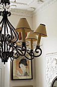 A chandelier with beaded ornaments and yellowed lamp shades