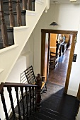 An old stairway - dark wooden banisters and floor boards with a view through an open doorway into a living room
