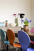 Coloured chairs at a dining table and storage jars on a wooden country-style chest of drawers