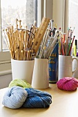 Knitting needles in white clay pots and various balls of wall