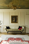 An elegant chaise longue in front of a white, wooden-panelled wall hung with a picture in an old-fashioned living room with a painted ceiling