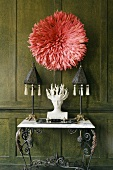 Coral-coloured wall decoration on a dark wood-panelled wall and black metal table lamps a white bust on a marble top wall table