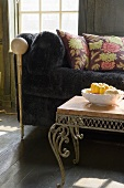 A dark plush sofa with cushions and a filligree occasional table with a bowl on it