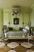 An elegant antique bed in front of a green wood panelled wall in a room with a painted wooden floor