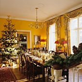 A Christmas party in a dining room of an English country-house with floor-to-ceiling windows and yellow walls