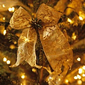 A gold embroidered bow on a Christmas tree