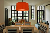 A pleated orange lampshade above a light coloured dining table and chairs in front of a bank of windows with black frames