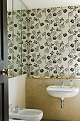 A bidet and a wash basin in a mini bathroom and black and white patterned wallpaper