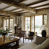 An elegant country house with a rustic wood beam ceiling and leather chairs in front of open swing doors leading to a terrace