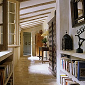 A terracotta floor in the hallway of a country house with a concrete shelf and a rustic wood beamed ceiling