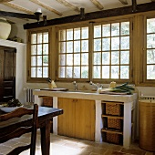 A stone kitchen counter in front of transom windows in a country house