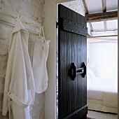 A rustic country house - a bathrobe on a hook next to an open, grey wooden door with a view of a four-poster bed