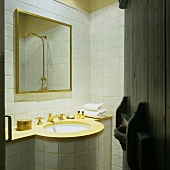 A view into a white tiled bathroom with a round basin with brass taps and a gold-framed mirror