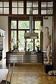 Blick durch Öffnung auf Edelstahlküchenblock mit Dunstabzug vor Terrassentüren