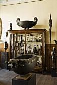 Metallschale auf einer Stele und Vitrinenschrank mit afrikanischer Kunsthandwerkssammlung