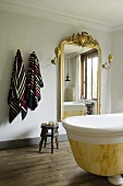 A bathroom in a country house with a free-standing antique bathtub and a wall mirror with a golden frame