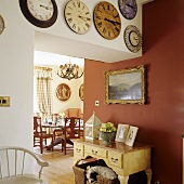A collection of antique wall clocks above a doorway with a red wall and view onto a dining table