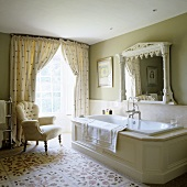 A spacious, traditional English country house-style bathroom with floor-to-ceiling windows and a comfortable armchair