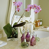 Pink orchids in glass vases and assorted flacons on a washstand