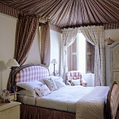 A bedroom in a traditional English country house - a fabric-covered ceiling and a bed with a small canopy